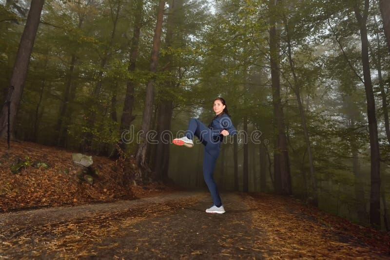 Meisje die de oefening van de knieschop doen tijdens kickboxing opleiding in een mi royalty-vrije stock foto