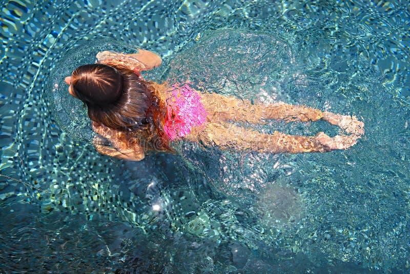 Meisje die in de openluchtpool zwemmen stock foto
