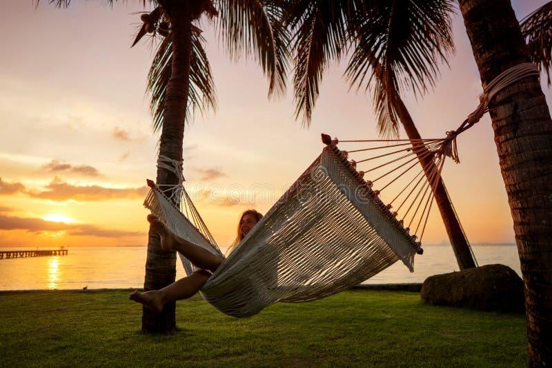 Meisje die in de palmen van een hangmatlast van een tropische vakantie genieten royalty-vrije stock foto