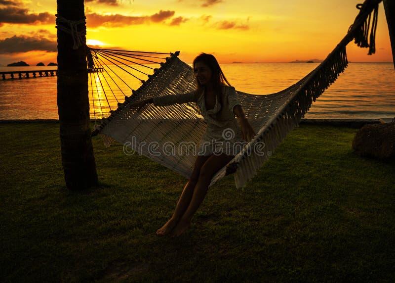 Meisje die in de palmen van een hangmatlast van een tropische vakantie genieten stock afbeelding