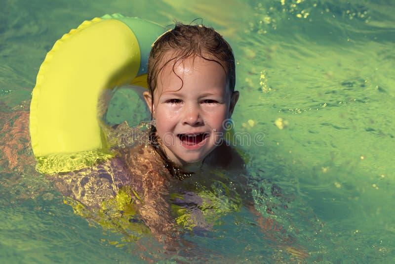 Meisje die in de pool in een cirkel zwemmen stock afbeeldingen