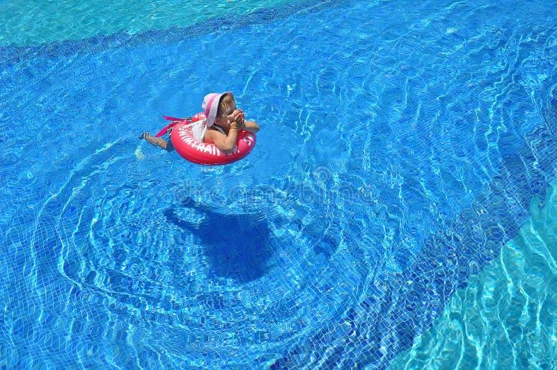 Meisje die in de pool in opblaasbare ring zwemmen royalty-vrije stock foto's