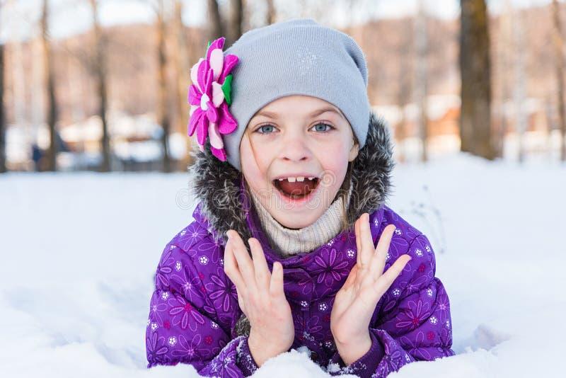 Meisje die in de sneeuw liggen stock afbeeldingen
