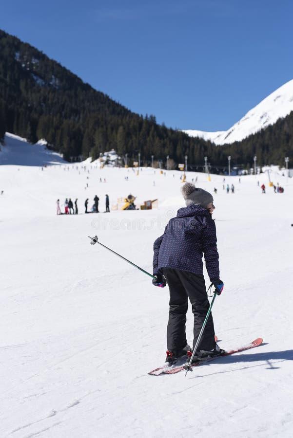 Meisje die in de sneeuw in de winter ski?en Jong geitje gekleed in blauw het ski?en toestel Hemel bij Bunderishka-polyana, skiërs stock afbeelding