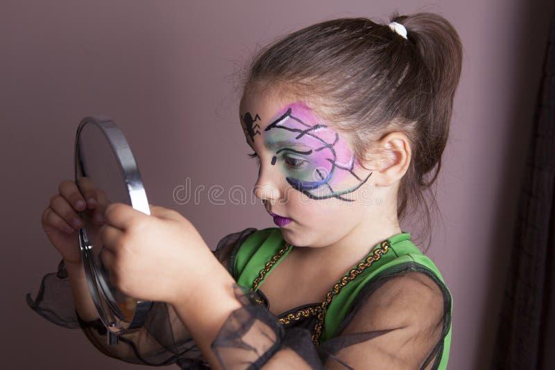 Meisje die de spiegel na gezicht het schilderen zitting onderzoeken stock foto's