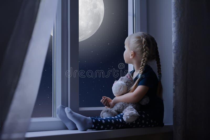 Meisje die de sterrige hemel en de maan bekijken stock foto