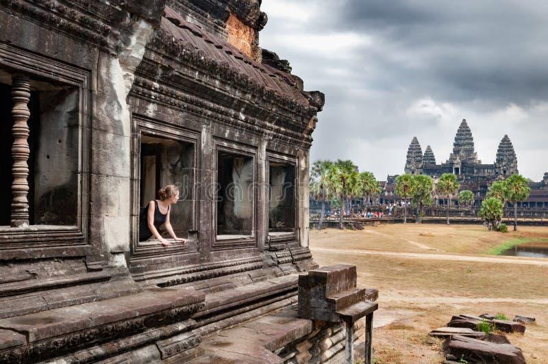 Meisje die de tempel van Angkor Wat in Kambodja bekijken stock foto
