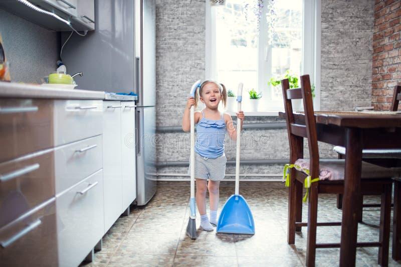 Meisje die de vloer in de keuken vegen stock foto