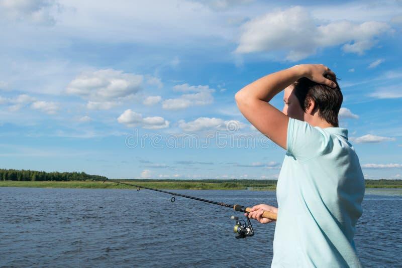 Meisje die denken hoe te een vis te vangen op het spinnen in goed weer op de rivier stock afbeeldingen