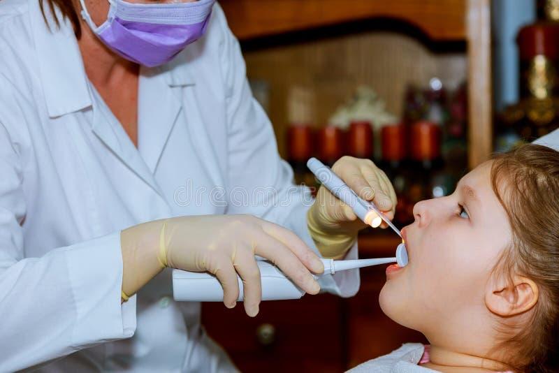 meisje die in dentist& x27 glimlachen; s stoel kindmond wijd open in dentist& x27; s stoel royalty-vrije stock foto