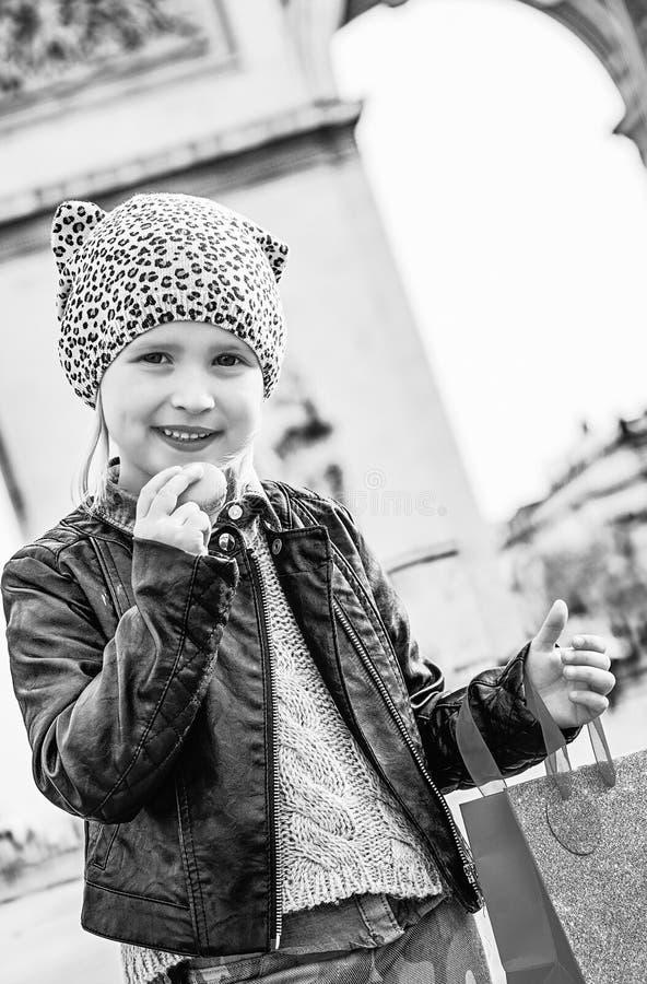 Meisje die dichtbij Arc de Triomphe in Parijs Franse makaron houden stock foto's