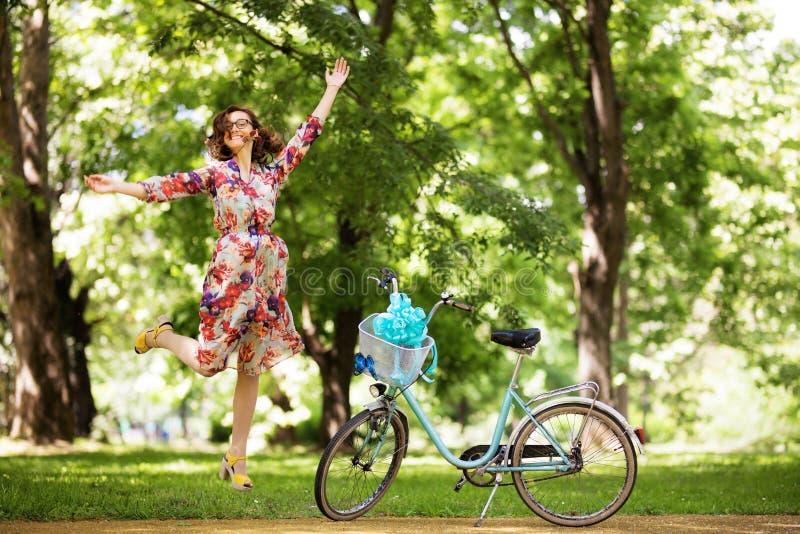Meisje die dichtbij haar uitstekende fiets springen stock foto