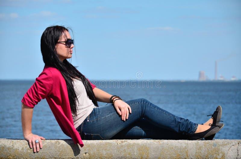 Meisje die dichtbij het overzees liggen royalty-vrije stock afbeelding