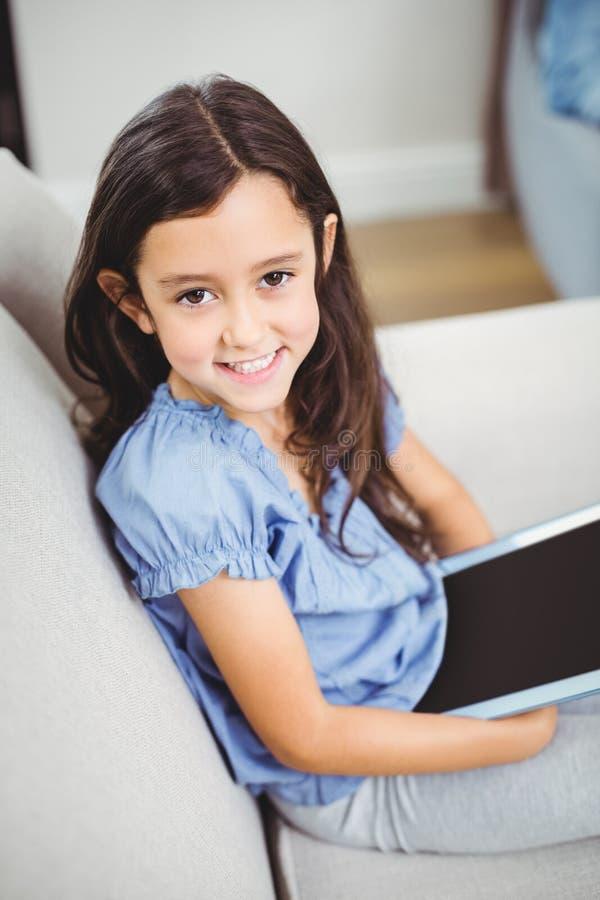 Meisje die digitale tablet gebruiken terwijl thuis het zitten op bank stock afbeeldingen