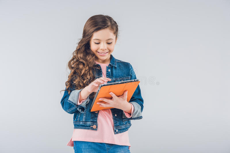 Meisje die digitale tablet op grijs gebruiken stock foto's