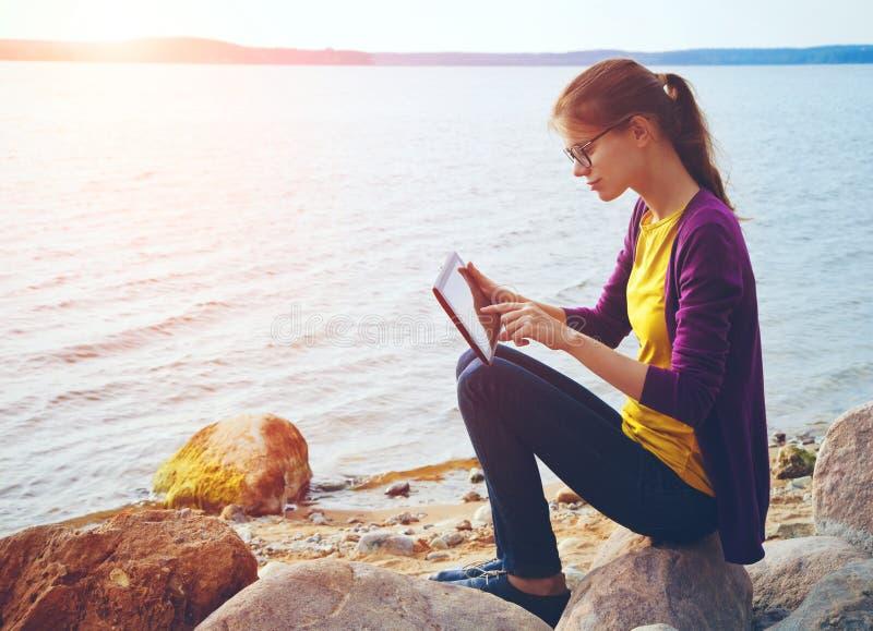 Meisje die digitale tablet op zee gebruiken stock afbeeldingen