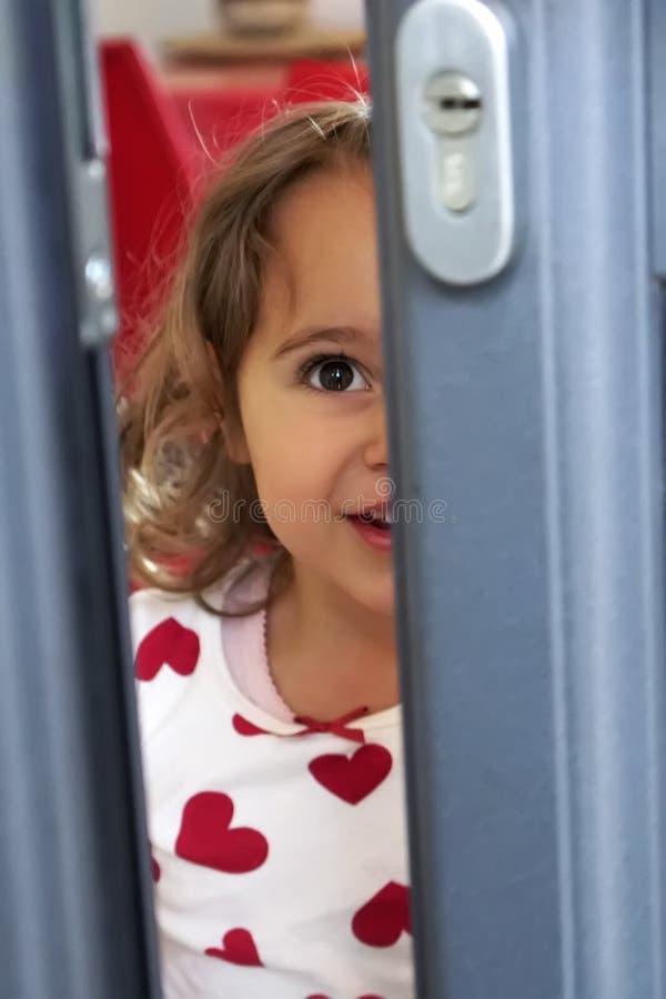 Meisje die door de open deur kijken royalty-vrije stock afbeeldingen