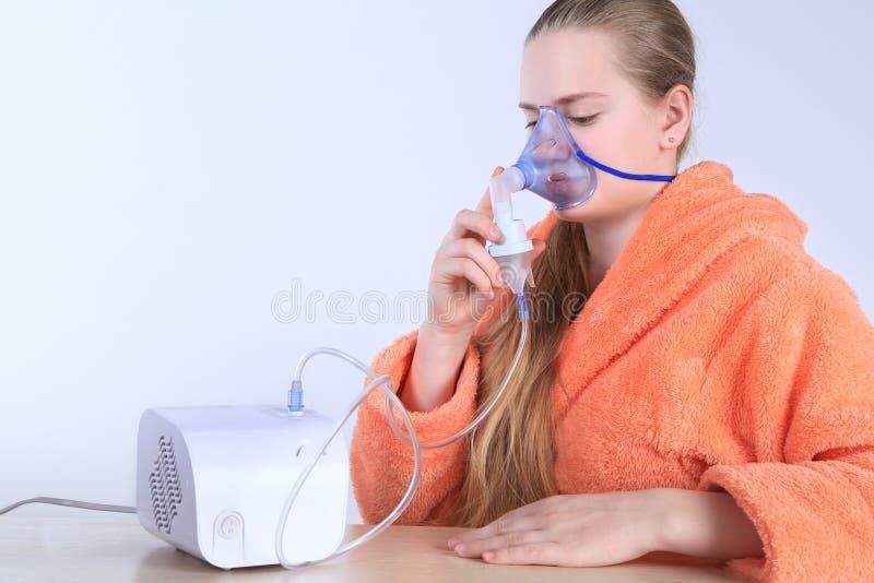 Meisje die door een stoomverstuiver ademen Geïsoleerdj op witte achtergrond royalty-vrije stock fotografie
