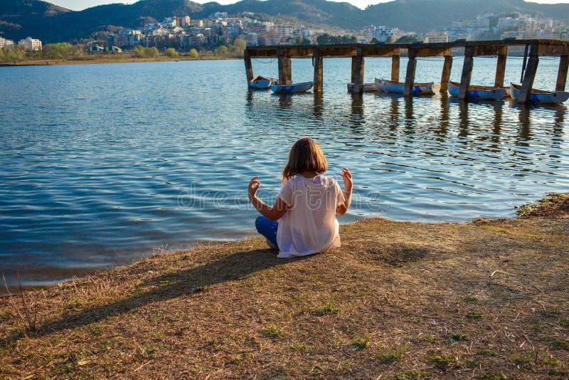 Meisje die door het meer tijdens het gouden uur mediteren stock afbeelding