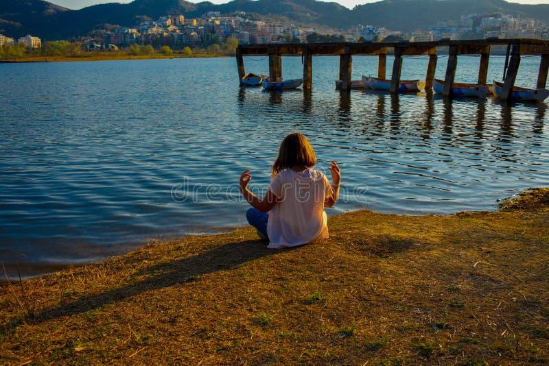 Meisje die door het meer tijdens het gouden uur mediteren royalty-vrije stock foto