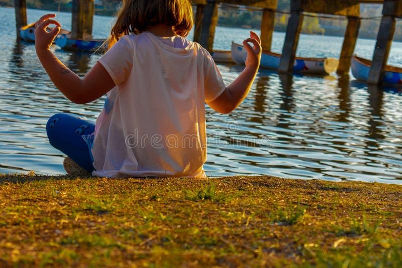 Meisje die door het meer tijdens het gouden uur mediteren stock foto