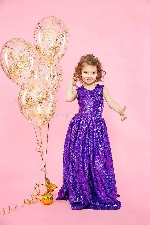 Meisje die duimen tonen bij feestelijke ballons stock foto