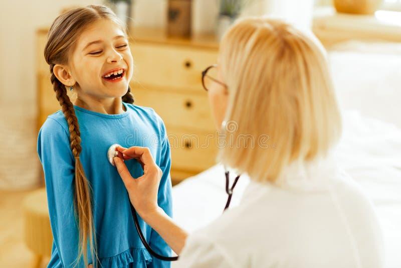 Meisje die een adem nemen terwijl een pediater die haar longen controleren royalty-vrije stock fotografie