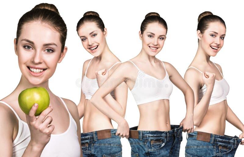 Meisje die een appel houden en grote jeans dragen stock afbeeldingen