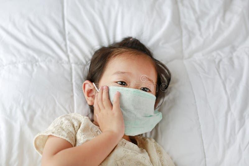 Meisje die een beschermend masker dragen die op het bed liggen stock afbeelding