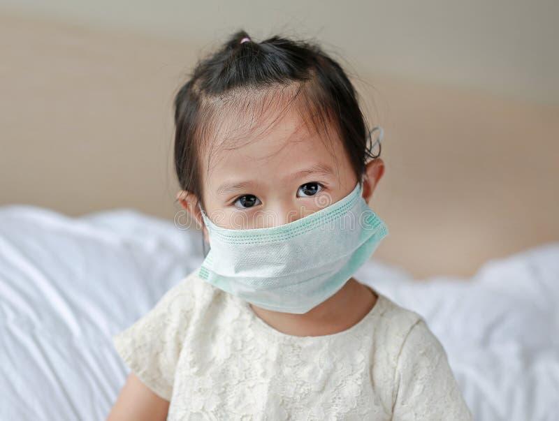 Meisje die een beschermend masker dragen die op het bed liggen royalty-vrije stock afbeelding