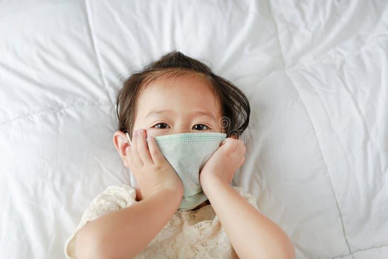 Meisje die een beschermend masker dragen die op het bed liggen royalty-vrije stock fotografie