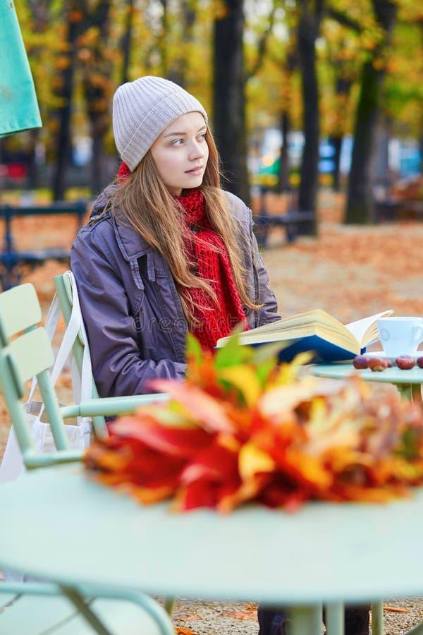 Download Meisje Die Een Boek In Een Openluchtkoffie Lezen Stock Foto - Afbeelding bestaande uit frankrijk, parijs: 54090880
