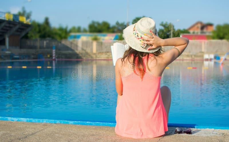 Meisje die een boek lezen door de pool royalty-vrije stock foto