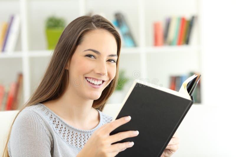 Meisje die een boek lezen en camera bekijken stock afbeeldingen