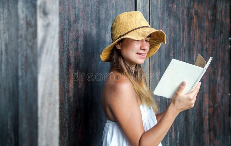 Meisje die een boek lezen tegen een muur in de straat stock fotografie