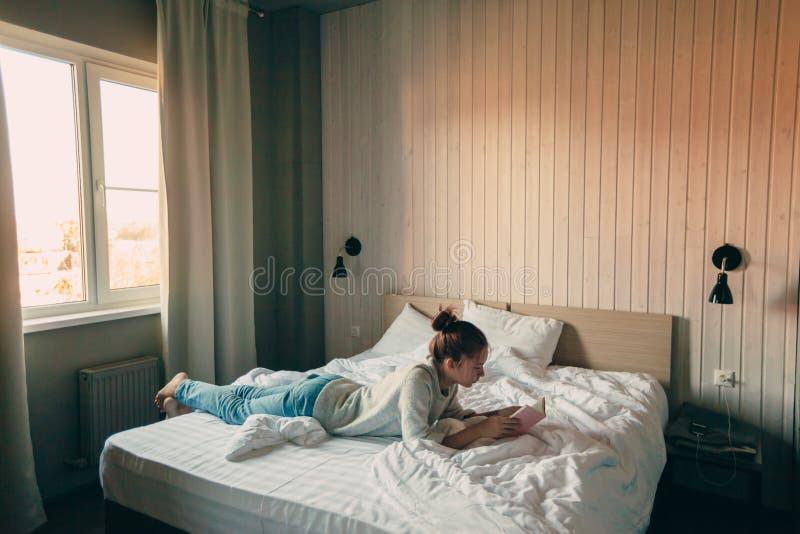 Meisje die een boek in slaapkamer lezen stock afbeelding