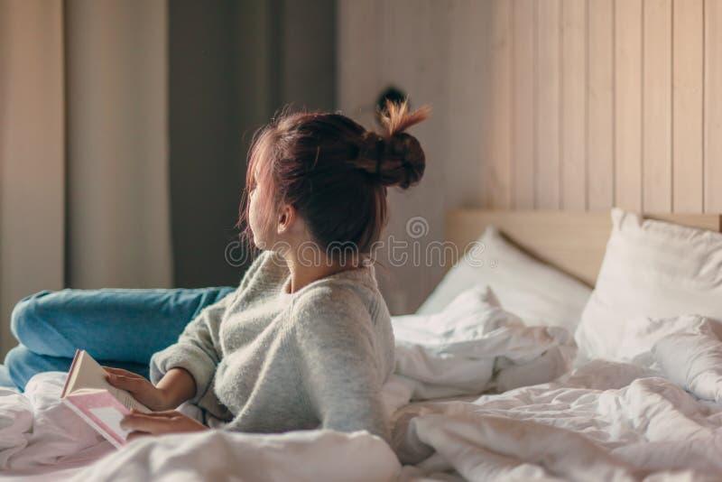 Meisje die een boek in slaapkamer lezen stock foto