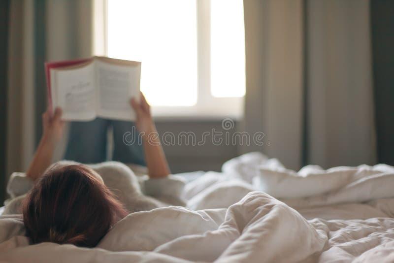 Meisje die een boek in slaapkamer lezen stock foto's