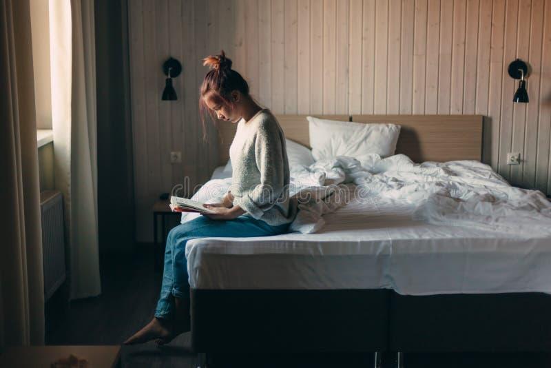 Meisje die een boek in slaapkamer lezen royalty-vrije stock afbeeldingen