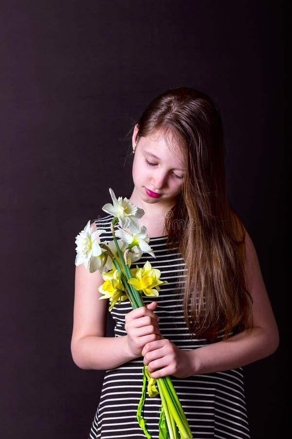 Meisje die een boeket van gele en witte gele narcissen houden stock foto's