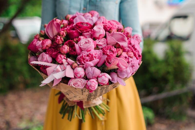 Meisje die een boeket van roze bloemen houden stock fotografie