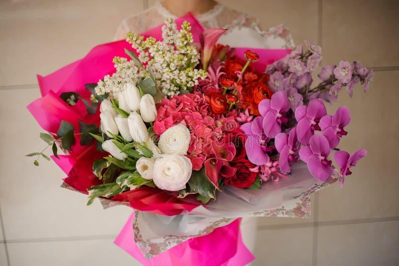 Meisje die een boeket van witte tulpen en lilac, roze orchideeën en hydrangea hortensia's en rode rozen houden royalty-vrije stock afbeelding