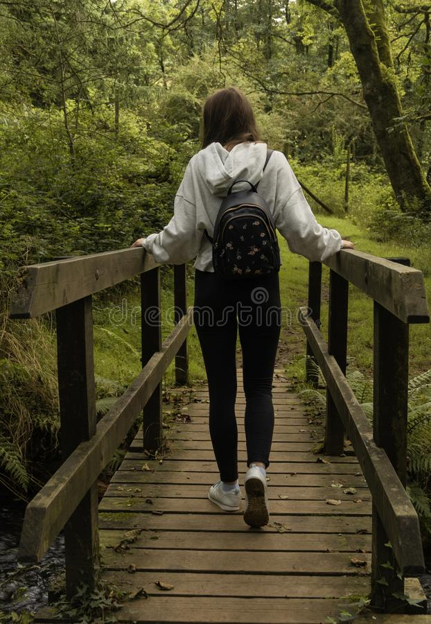 Meisje die die een brug kruisen van achter/Jong meisje met een rugzak wordt gefotografeerd die een brug in het bos kruisen stock afbeeldingen