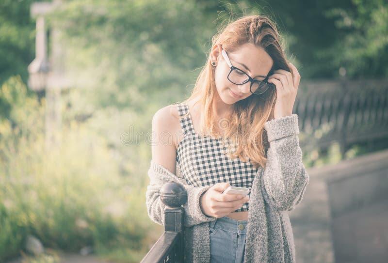 Meisje die een celtelefoon in openlucht met behulp van royalty-vrije stock fotografie