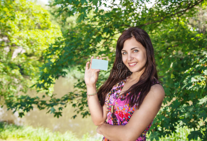 Meisje die een creditcard in het park houden stock afbeelding