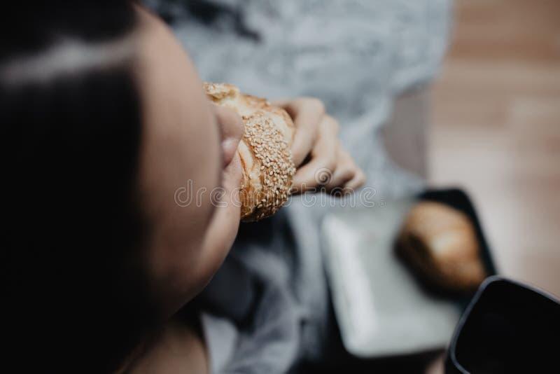 Meisje die een croissant bijten en een grijze badkabel dragen royalty-vrije stock afbeelding