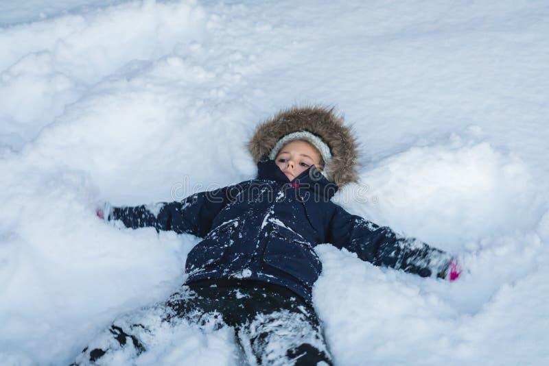 Meisje die in een diepe sneeuw liggen stock afbeeldingen