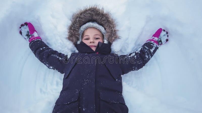 Meisje die in een diepe sneeuw liggen stock afbeelding