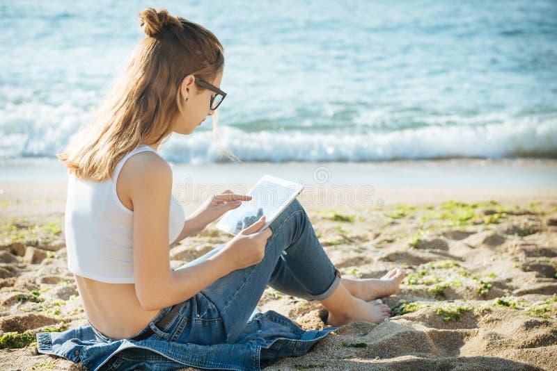 Meisje die een digitale tablet gebruiken door het overzees stock foto's
