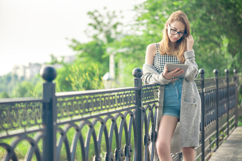 Meisje die een digitale tablet in openlucht gebruiken royalty-vrije stock afbeelding